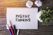Positive Thinking word with Notepad and green plant on wooden background.