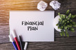 Financial Plan word with Notepad and green plant on wooden background.