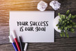 Your Success Is Our Goal word with Notepad and green plant on wooden background.