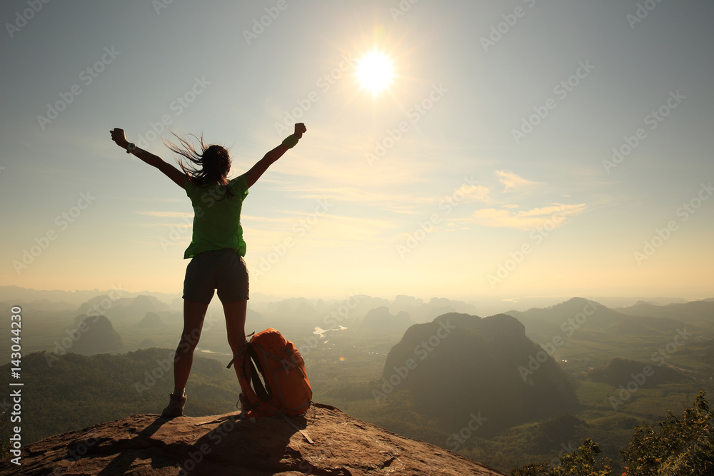 Fototapeta silhouette of cheering woman hiker open arms at mountain peak