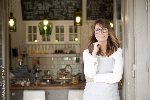 Proud small coffee shop owner businesswoman. Shot of a happy barista woman standing at doorway and inviting to her coffee shop. Small business.