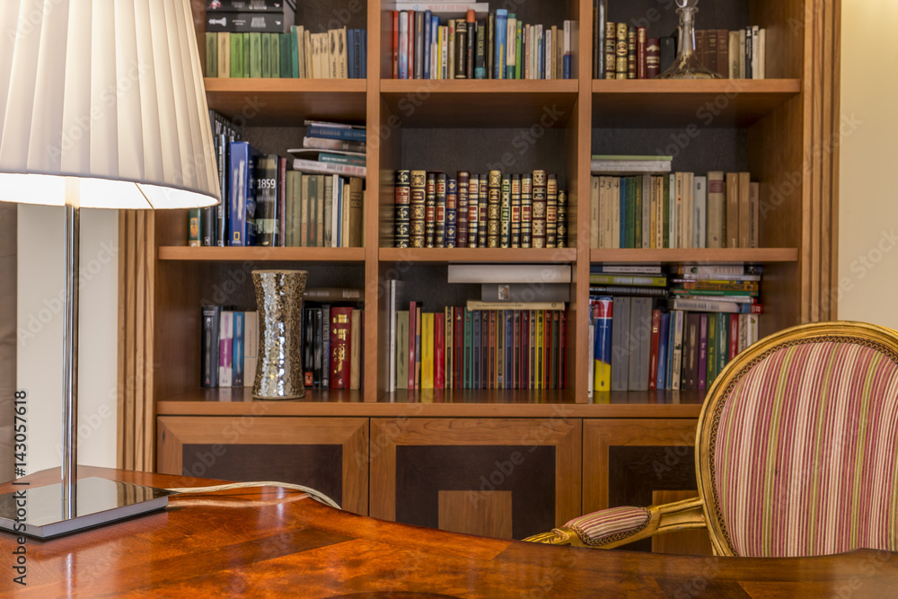 Fototapeta Wooden desk and classic bookcase with books