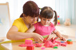 Cute kid and mother playing with sculpting toy at home. Little girl building sandcastle.