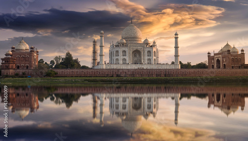 Poster Artistique Taj Mahal Agra at sunset as seen from the Yamuna river banks with a moody sky. Taj Mahal designated as a World Heritage Site is a masterpiece of Indian heritage and architecture.