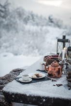 Coffee, Biscuits, Copper Colour Tea Pot On Snow Covered Picnic Bench