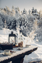 Cup Of Coffee And Biscuits On Snow Covered Picnic Bench