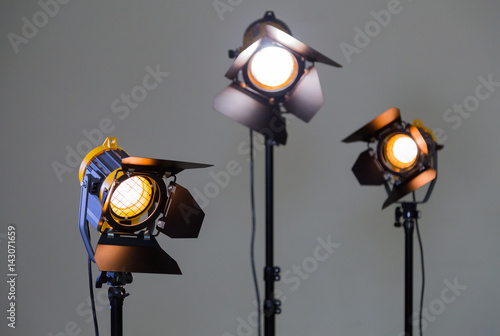 Foto op Canvas Licht, schaduw Three halogen spotlights with Fresnel lenses on a grey background. Photographing and filming in the interior. Lighting equipment for movie production.