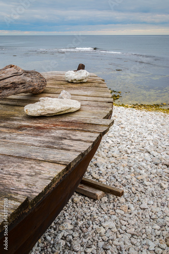 Fotografía  Skiff boat on stone beach by the ocean with stones on boat cover on Gotland, Swe
