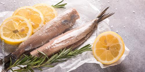 Plakat Świeżo solony śledź z solą, cytryna i rozmaryn na szarym tle. Tradycyjny holenderski przysmak. Styl retro toned.