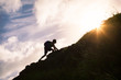 canvas print picture - Young man climbing up a mountain. Self improvement and life goals concept.