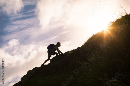 Photo Young man climbing up a mountain