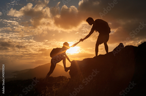 Платно Male and female hikers climbing up mountain cliff and one of them giving helping hand