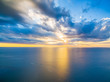 Aerial panoramic view of lonely boat sailing across ocean at beautiful sunset. Beautiful glowing yellow light reflecting in blue bay waters