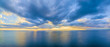 Aerial panoramic view of ocean water and beautiful blue skies at glowing yellow sunset. Nothing but water and clouds