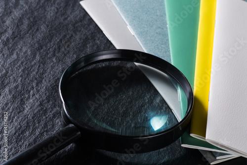 Foto  黒背景に虫眼鏡とカラフルなノート