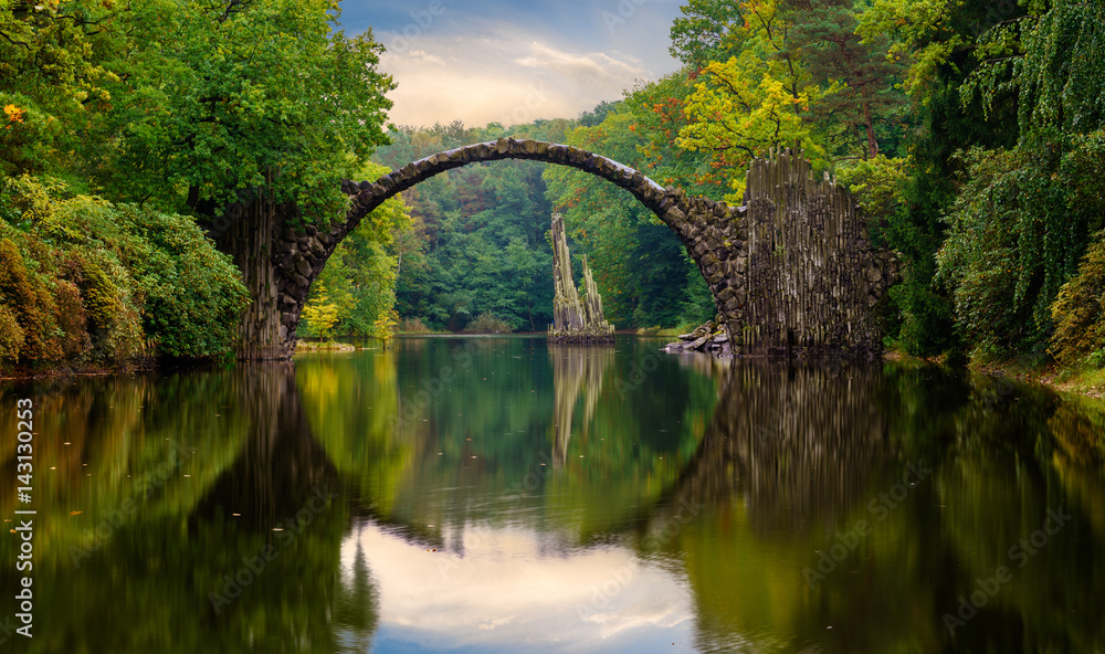 Fototapeta Autumn, cloudy evening over Devil's bridge in the park Kromlau, Germany