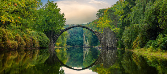 Fototapeta Mosty Autumn, cloudy evening over Devil's bridge in the park Kromlau, Germany