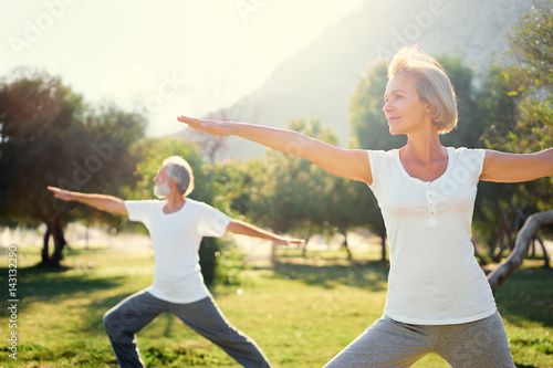Staande foto School de yoga Yoga at park. Senior family couple exercising outdoors. Concept of healthy lifestyle.