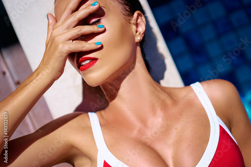 Sunstroke or suntan. Fashion colorful portrait of young woman in red swimsuit lying at swimming pool.