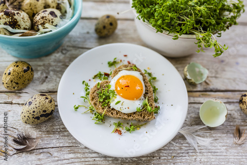 Roasted quail egg with cress on the bread on a wooden background.