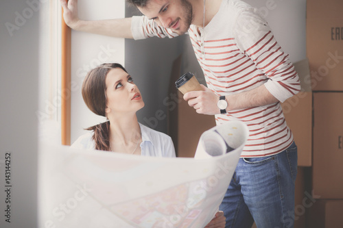 Fototapeta Young couple sitting on the floor and looking at the blueprint of new home obraz na płótnie