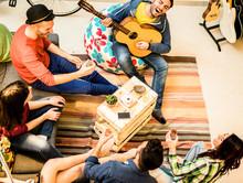 Group Of Trendy Friends Having Fun In Hostel Living Room
