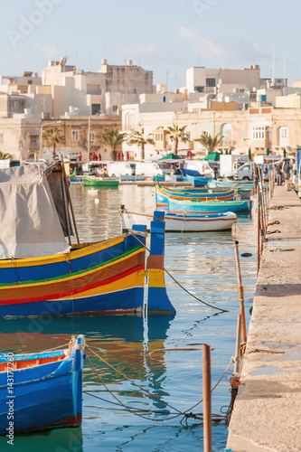 Photo Stands Nice Mediterranean traditional colorful boats luzzu. Fisherman village in the south east of Malta. Early winter morning in Marsaxlokk, Malta.