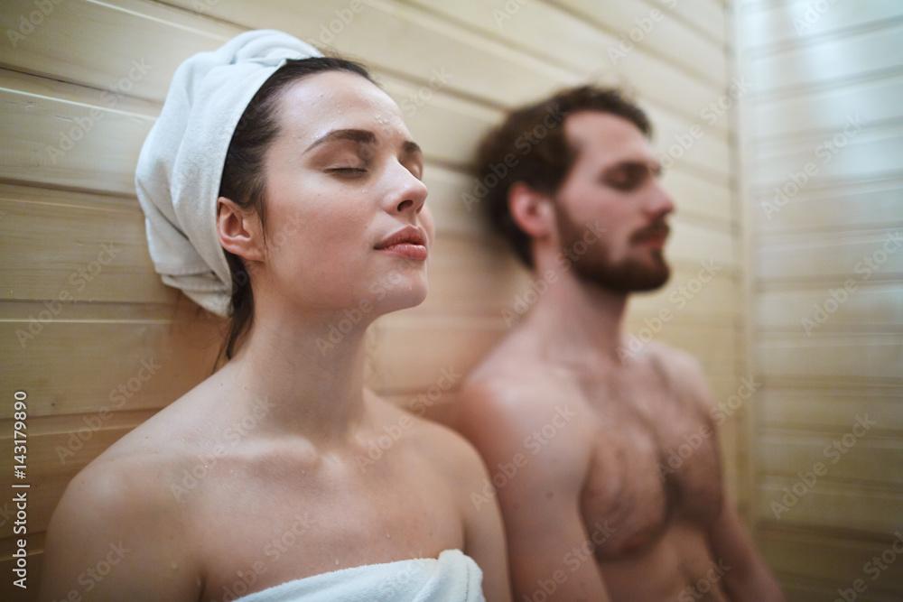 Fototapeta Pleased woman enjoying time in sauna with her husband