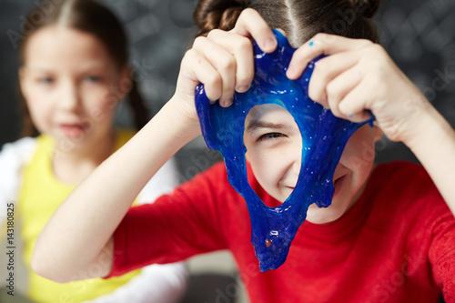Cuadros en Lienzo Happy kid looking through hole in blue slime