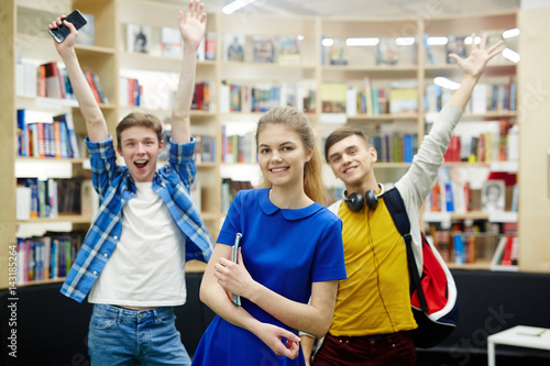 Group Of Three Hy Students Smiling Cheerfully And Raising Hands In Library Modern College