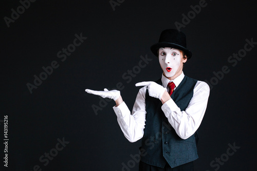 Mime shows at something invisible on his palm
