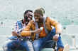 canvas print picture - Two black race friends having fun with mobile.