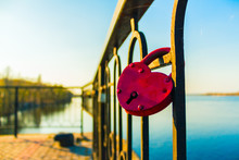 Red Padlock Of The Heart Shape On The Fence Of A River Wharf