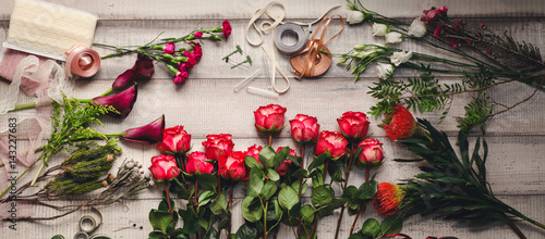 Carnations, red roses, purple callas on a wooden table in a flower shop