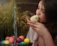 Young Girl Kisses A Chick. Basket With Easter Eggs.