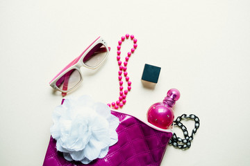 Obraz na płótnie Canvas Flat lay of pink bag open out with glasses and cosmetics, accessories on light gray background, fashion concept