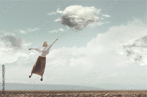 Photo woman flying in the sky carried by a cloud