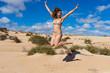 Spain, Canary Islands, Fuerteventura, Corralejo. Happy girl jump with hands up