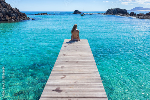 Poster Canary Islands Spain, Canary Islands, Fuerteventura, Isla de lobos. Topless girl on a pier clear transparent water