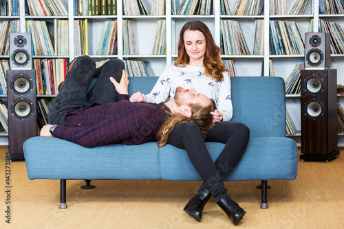 a man relaxing on the lap of his wife while listening to music Wallpaper Mural