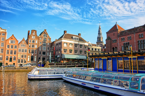 Photo Damrak Canal with boats and dancing houses in Amsterdam