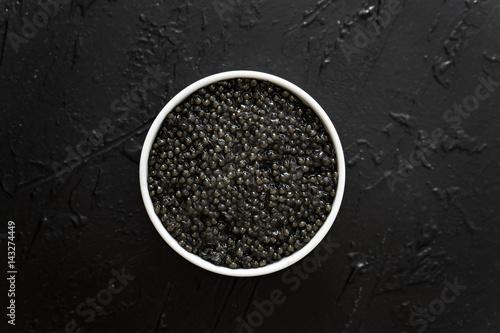 black caviar in white bowl  on black  background