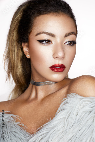 A young Asian girl with creative makeup, arrows and bright red lips with sparkles. A beautiful model with perfect skin in a fur coat made of artificial fur ...