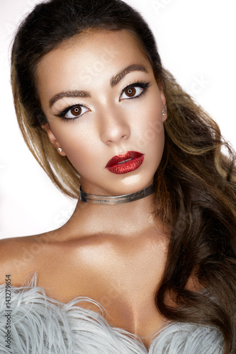 A young Asian girl with creative makeup, arrows and bright red lips with sparkles.