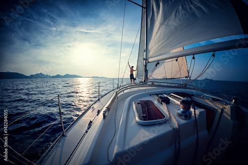 Młody człowiek pozycja na jachcie w morzu przy zmierzchem