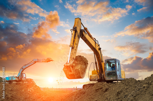 Stampa su Tela excavator in construction site on sunset sky background