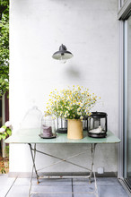 Terrace And Metal Table With Pots, Candle Holders, Chamomile Flowers And Various Flea Markets' Objects In A Vintage Atmosphere