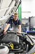 Portrait Automechaniker in der Werkstatt am Motor eines Fahrzeuges // Portrait of car mechanic in the workshop at the engine of a vehicle