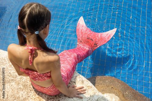 Fille de sirène avec queue rose sur le rocher au bord de la piscine mettre les p Poster