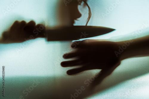 Fotografie, Obraz  der Schatten einer Frau mit einem Messer ist im Gegenlicht zu sehen